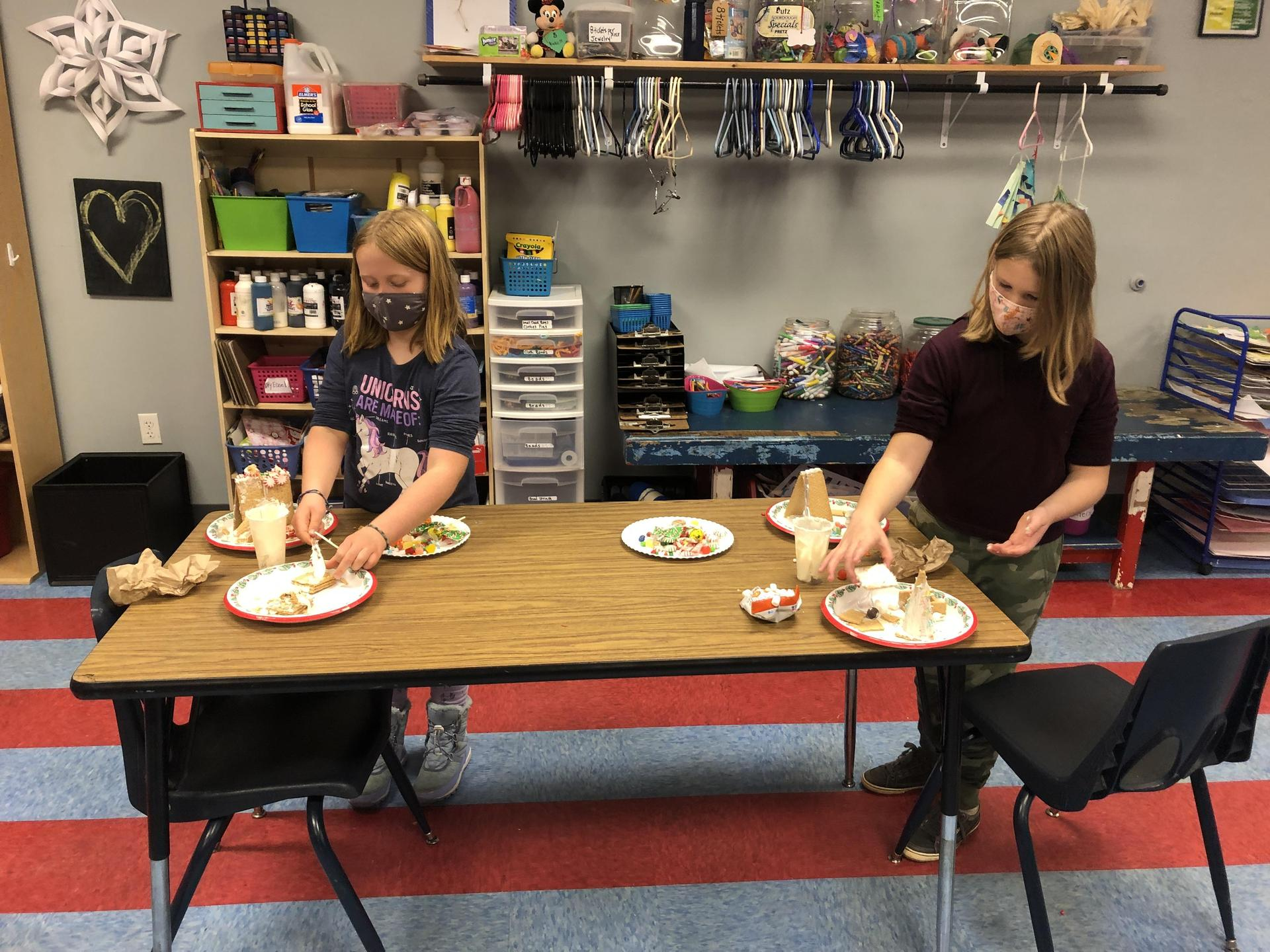 Two aftercare students make gingerbread houses