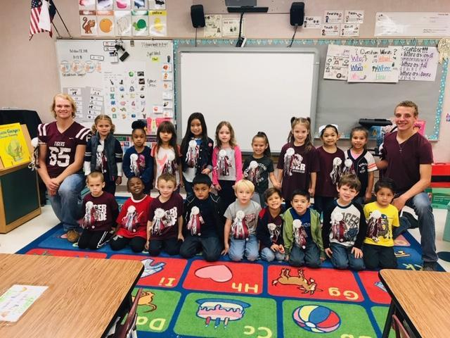 Kindergarten students with two high school students who made them mums for homecoming.