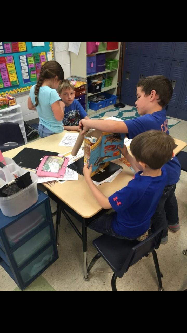 Students take turns and collaborate while working on a STEM project