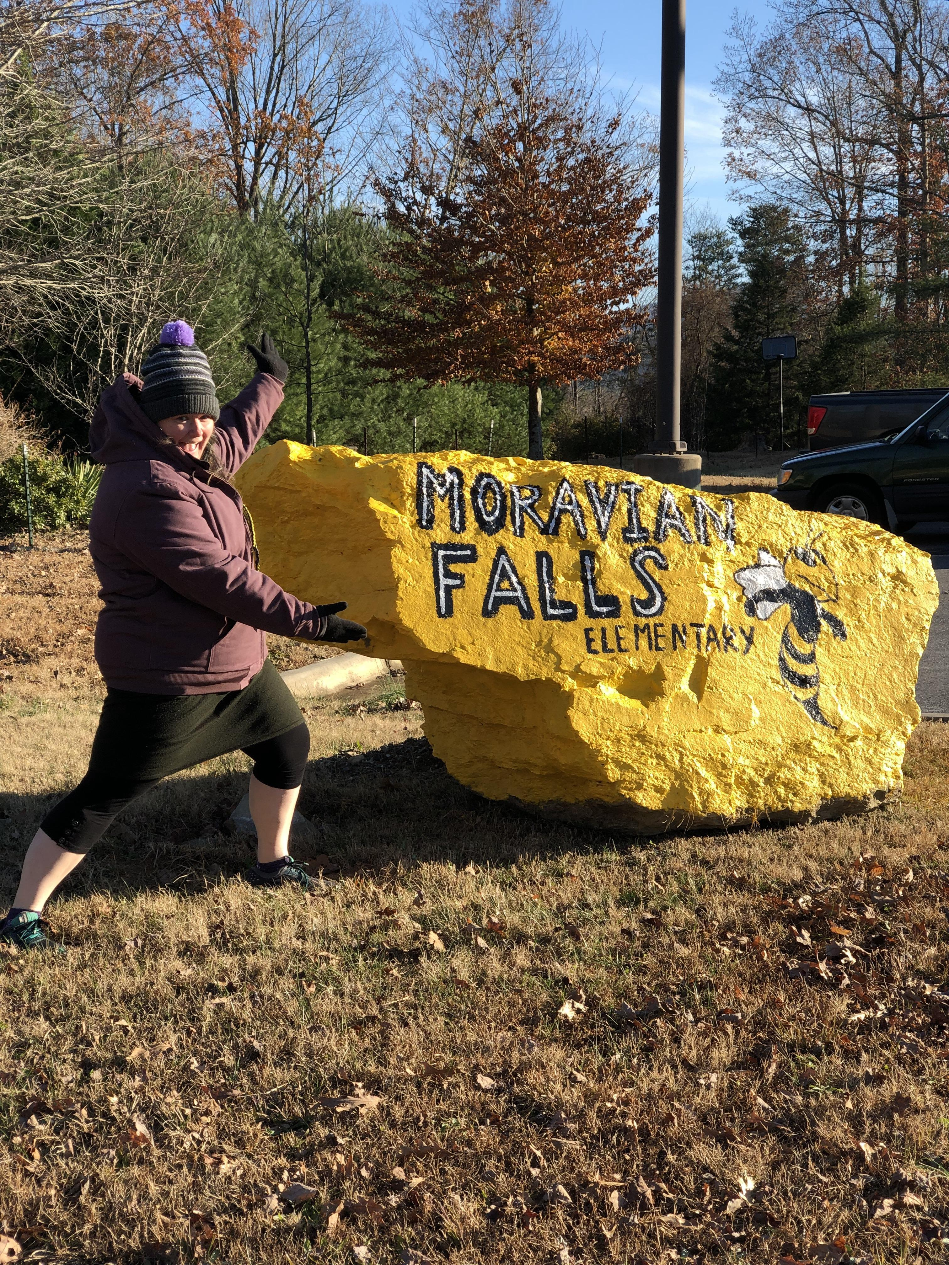 Art teacher poses with newly painted spirit rock.