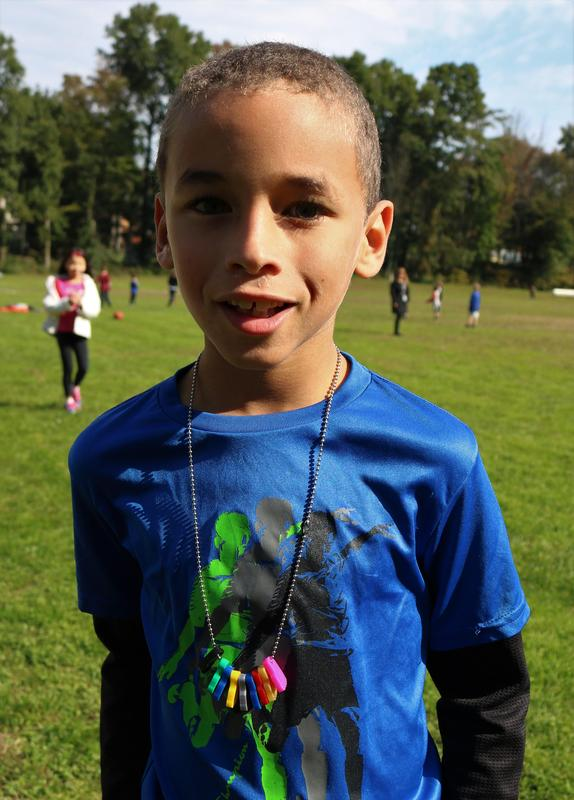 2nd grader at Tamaques shows off his charm necklace which he earned as a member of the Mileage Club.