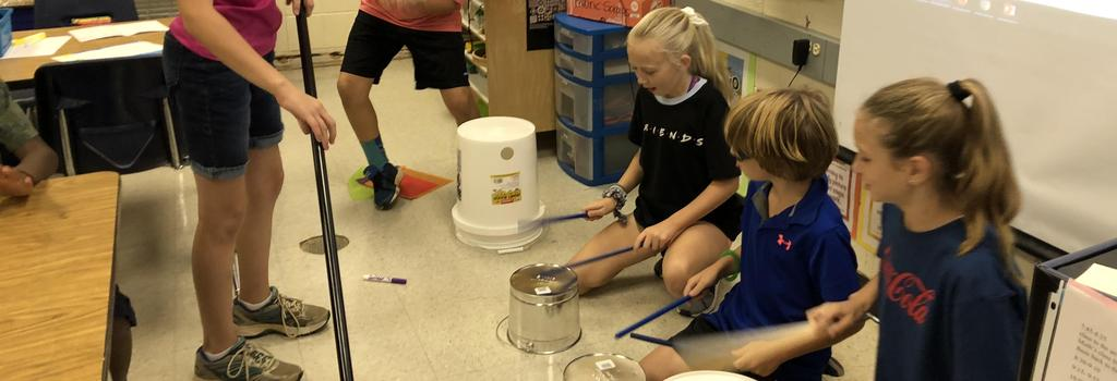 Students playing buckets like drums