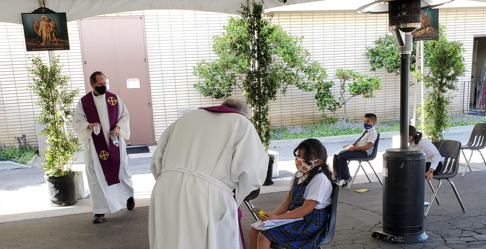 Our priests helping our second graders during their first reconciliation