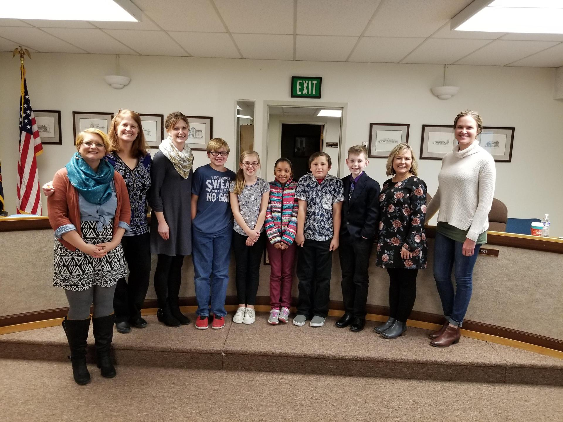 Endeavor Elementary students, Principal Heather Yarbrough and Trustees Allison Westfall, Janelle Stauffer and Heather Lewis pose at the board meeting.