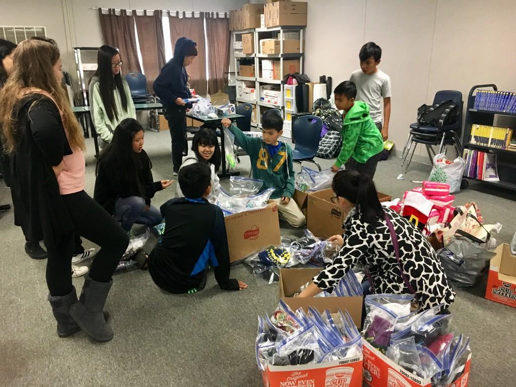 Parents and students sorting through boxes.