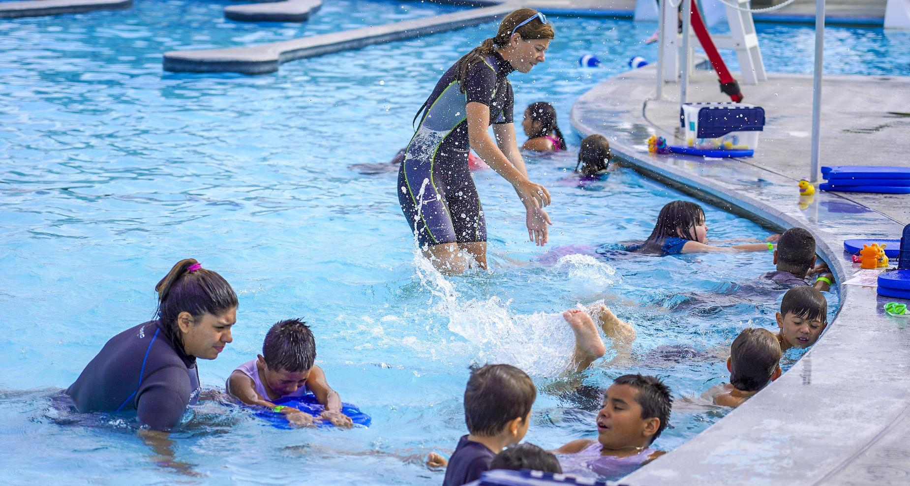 Second graders learning how to kick inside the swimming pool.