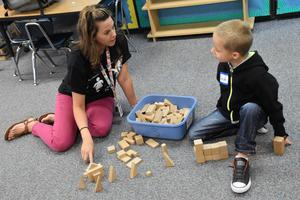 A kindergarten teacher playing blocks with a new student.