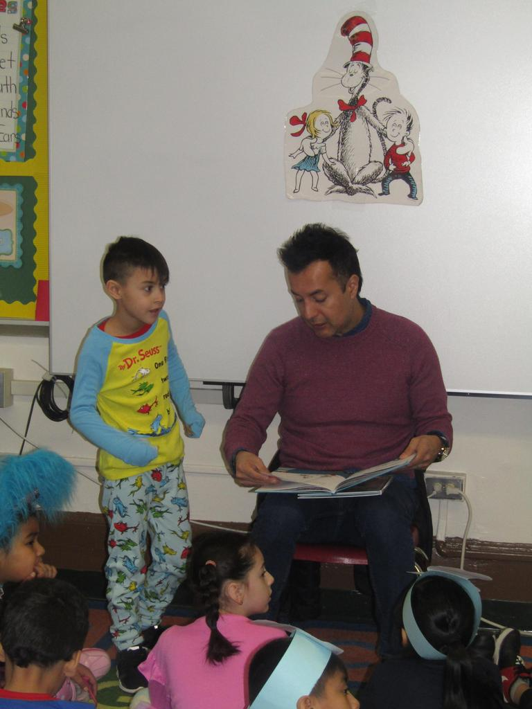 father with son next to him reading to the class