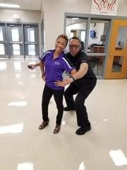 Mrs. Burns (Office Manager) and Mr. McKnight (Barber Instructor) posing for the camera