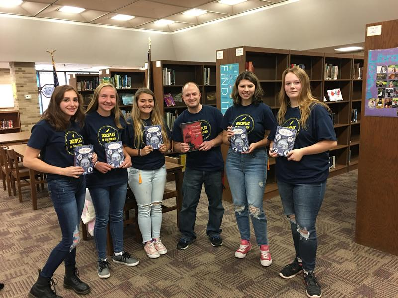 Five students and a teacher, each holding a book