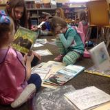 Students buddy reading with books on floor