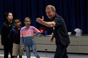 Laguna performer working with students