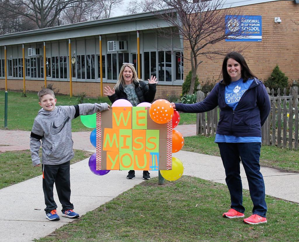 Photo of Washington teachers and student posing with sign before car parade for students during COVID-19 distance learning.