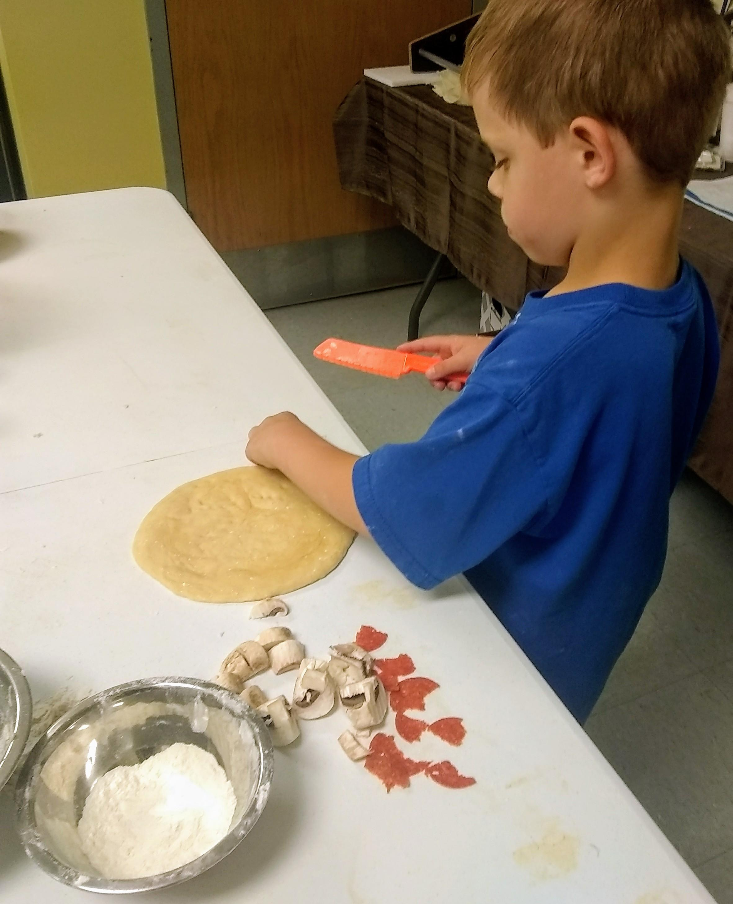 child shaping a pizza