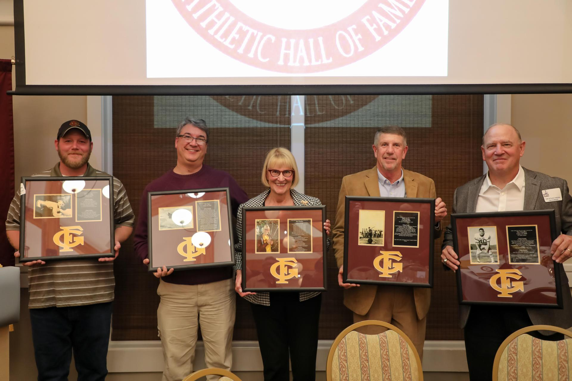 Hall of Fame Inductees holding award plaques