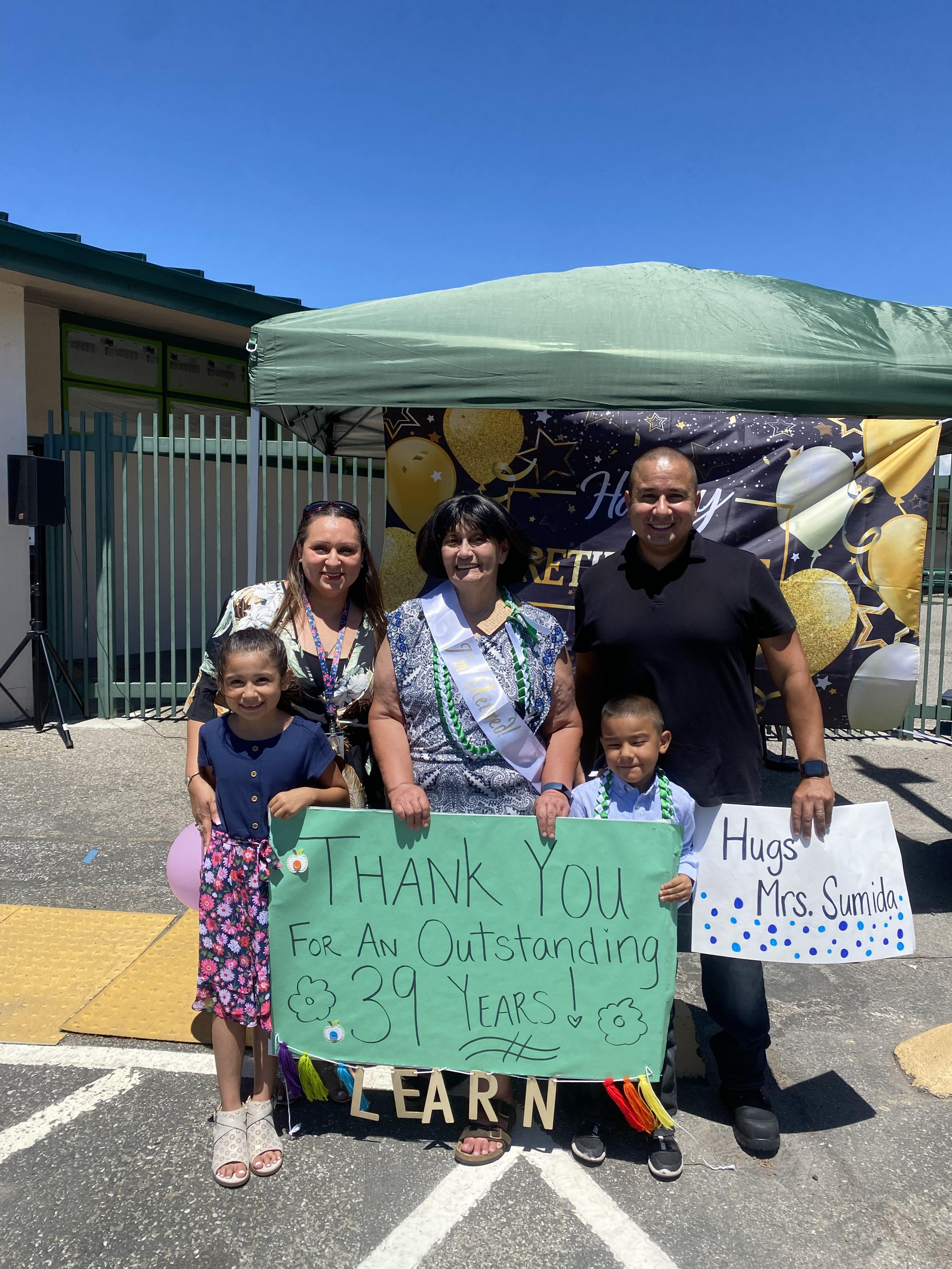 Mrs. Sumida and family with sign