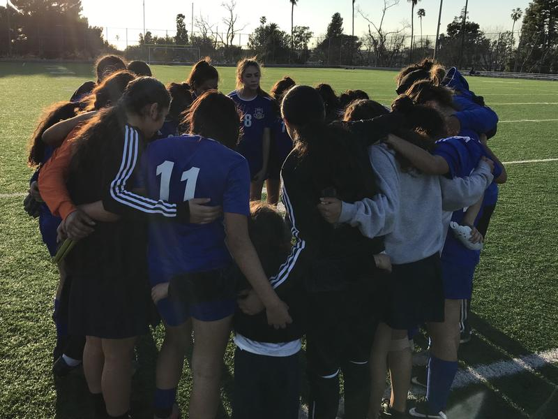 Girls soccer team in a huddle on a field