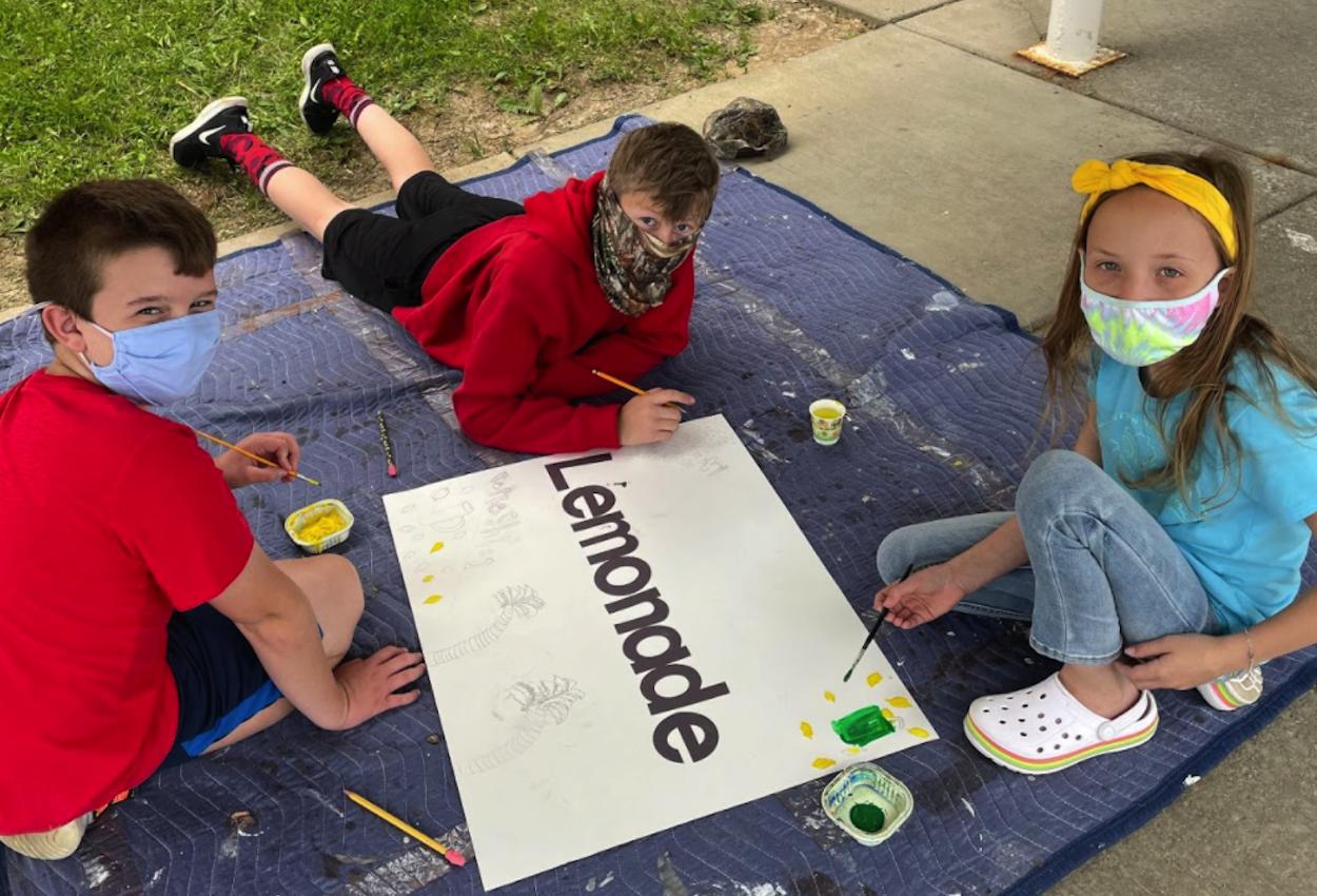 students paint signs outside
