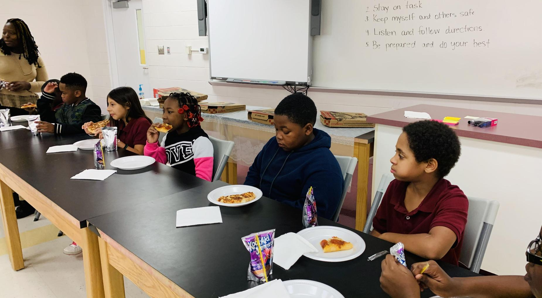 Students enjoying pizza with the principal