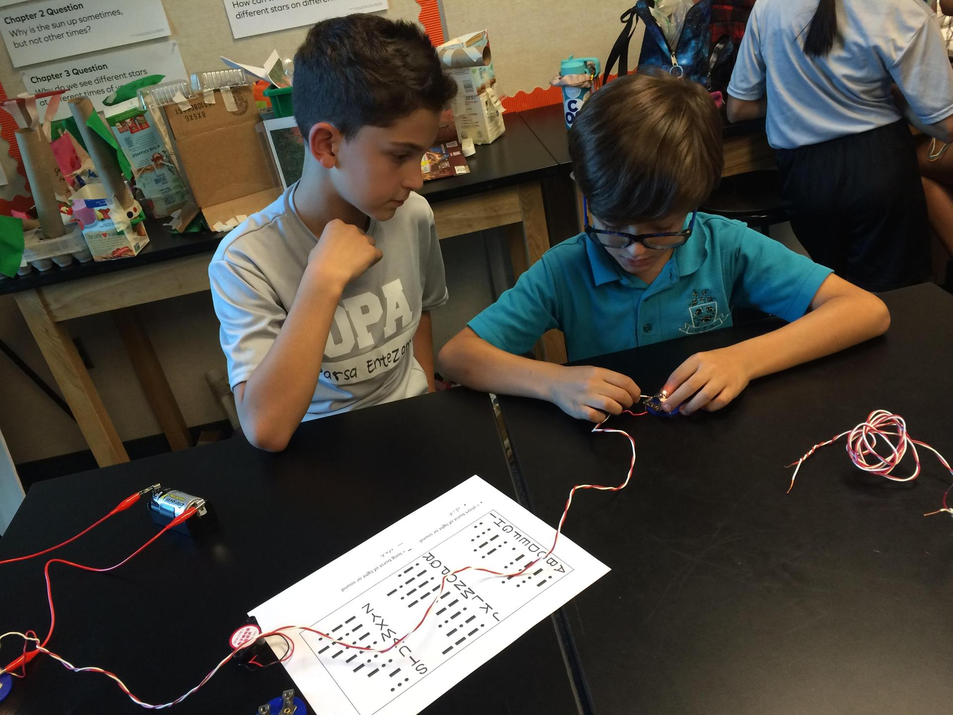 two boys building an electric circuit in parallel