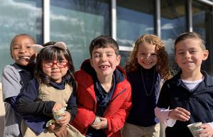 Students smile for the camera outside at recess.