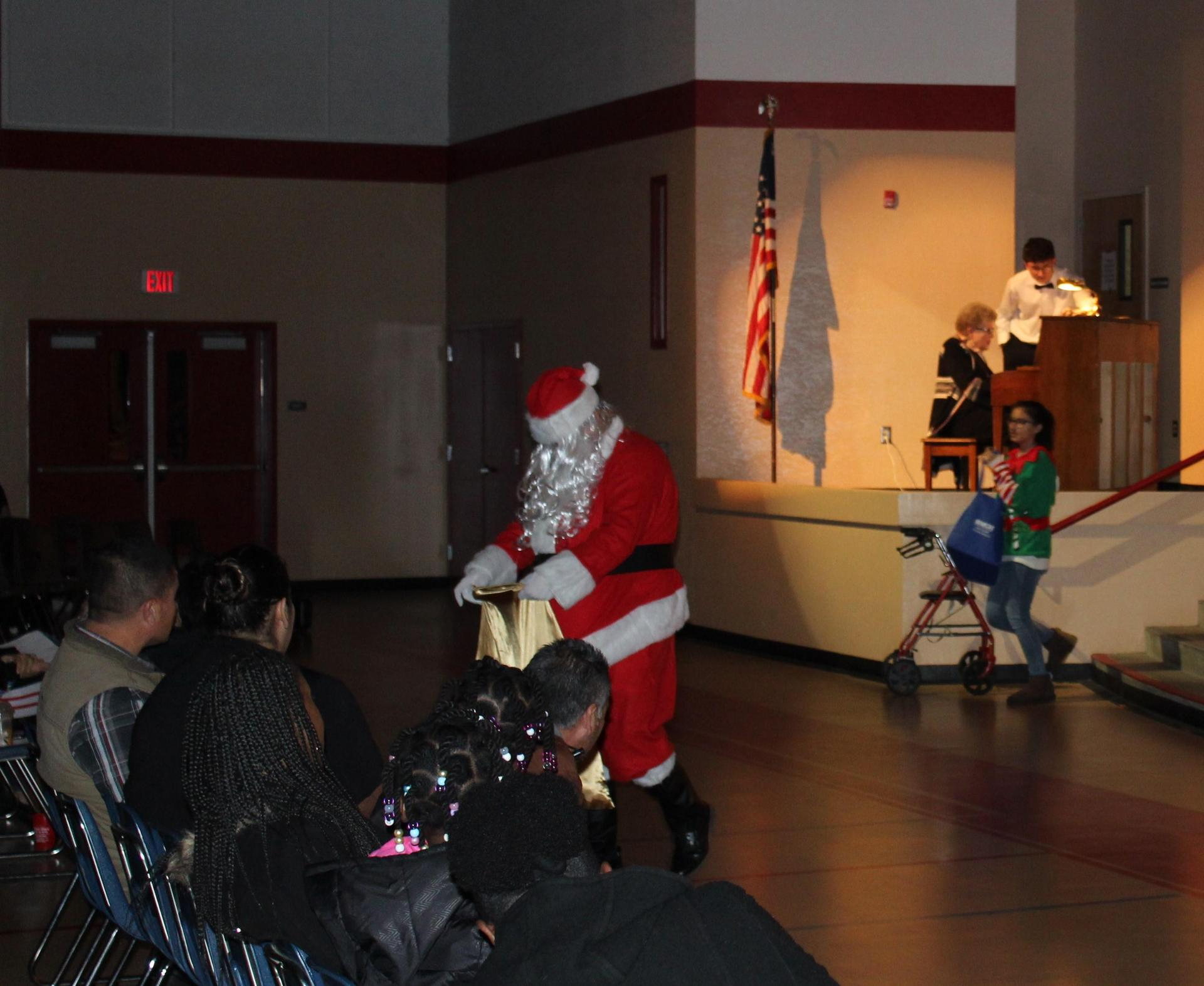 Santa gives gifts to the audience.