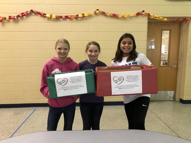 Three girls in be nice hold up donation boxes.