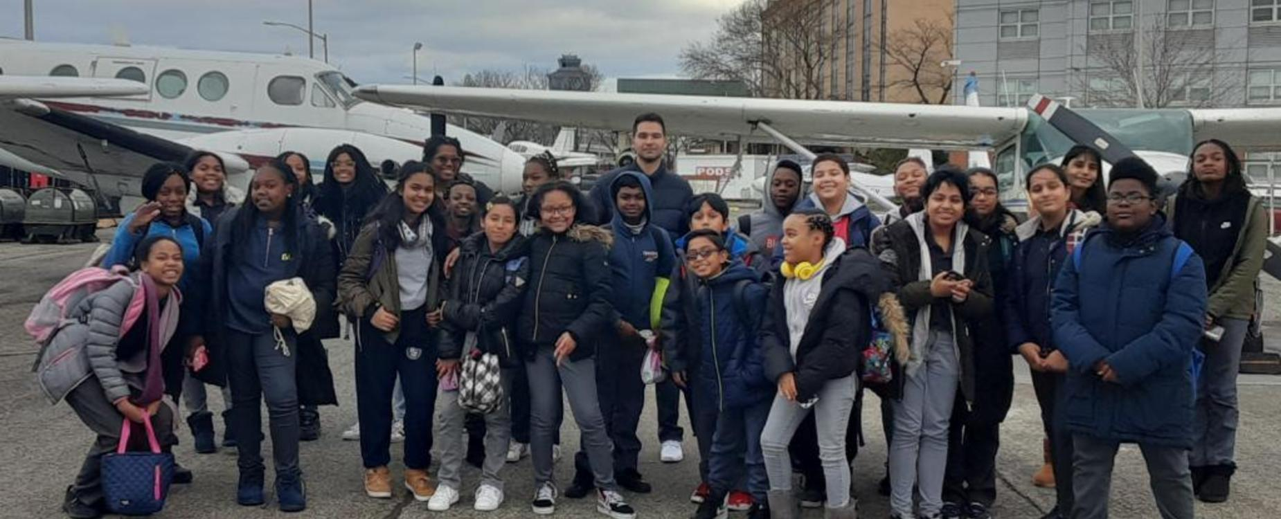 six graders on a college trip to Vaughn College in front of an airplane