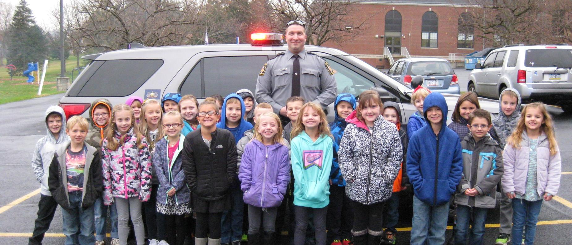Students with a state police trooper for career day.