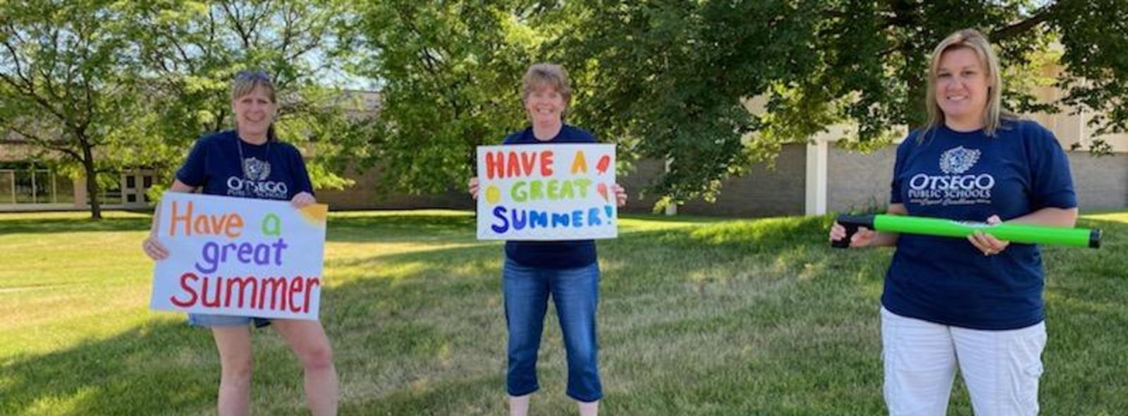 2nd grade teachers hold up signs saying have a great summer