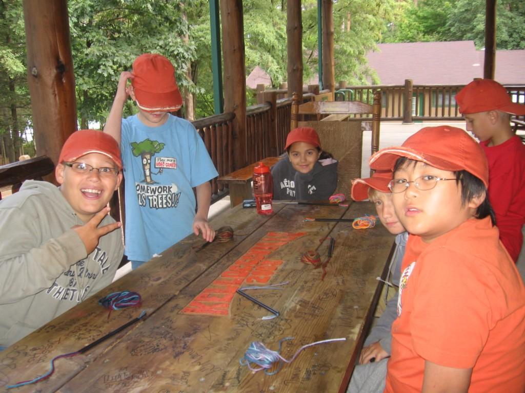 students make crafts on porch at cabin