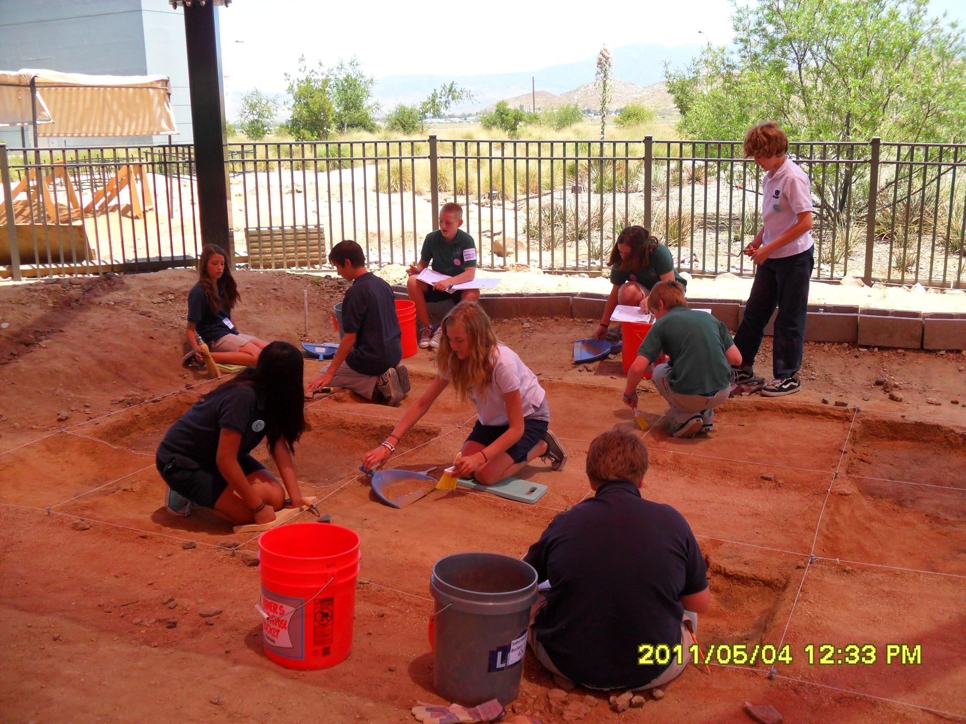 Students working in archaeology simulated dig site