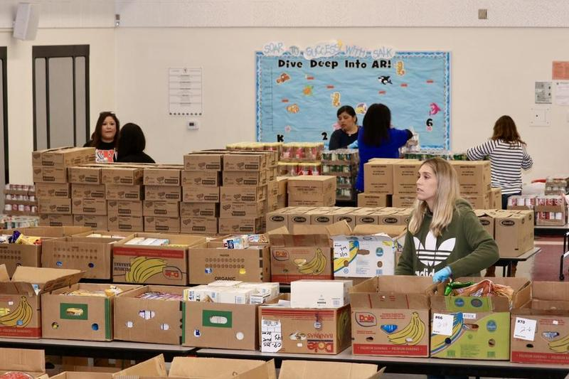 Magnolia School District Teachers Help Assemble Bags of Food