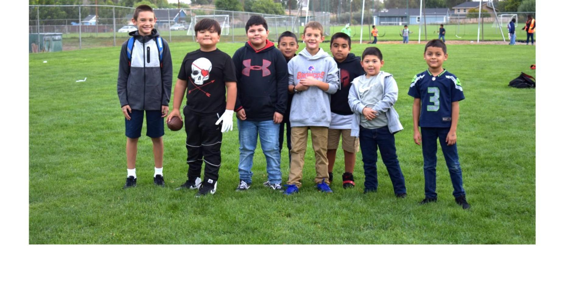 8 boys playing football at recess...and they are all smiling!