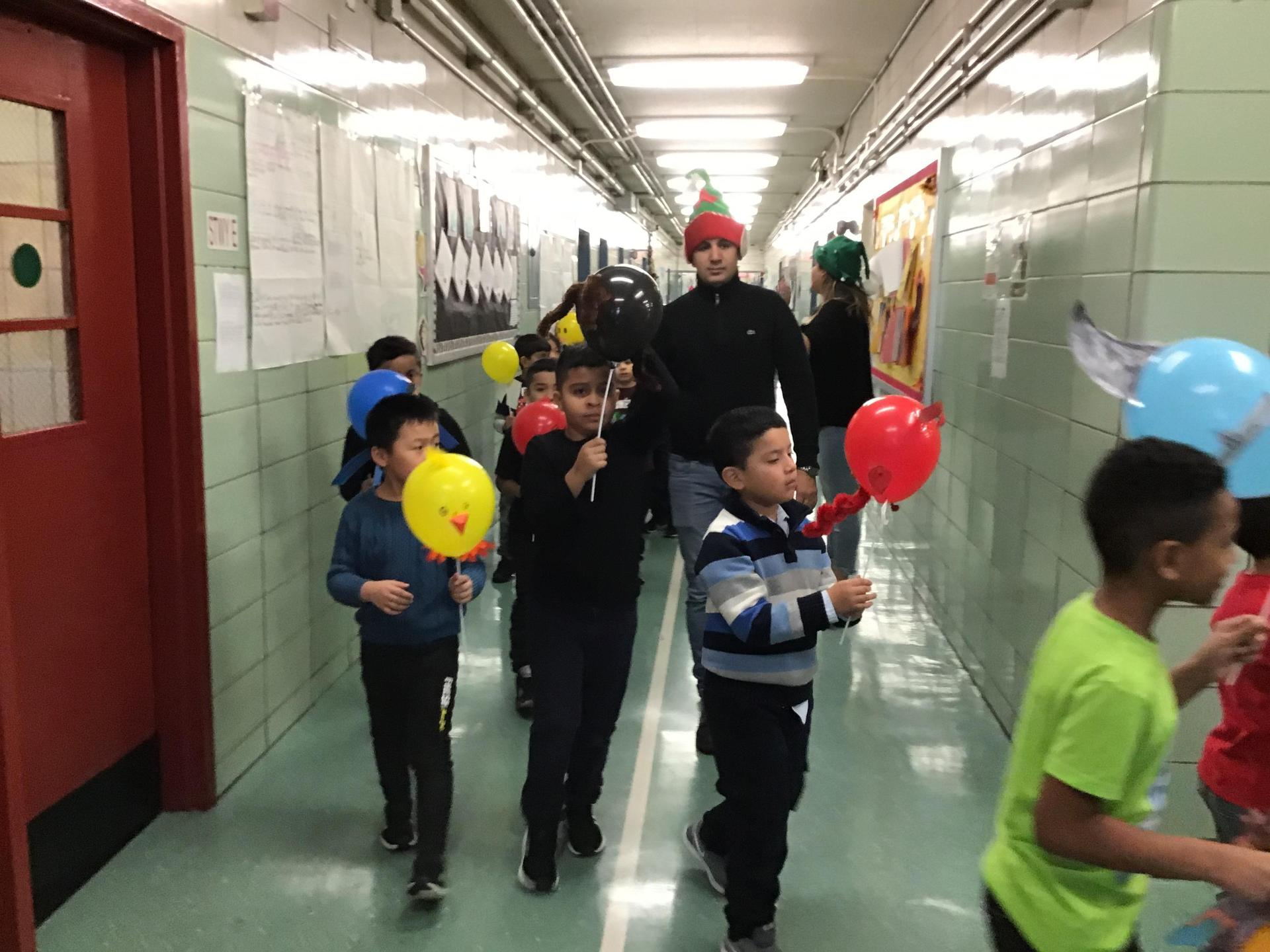 students parading in school hallway with balloons