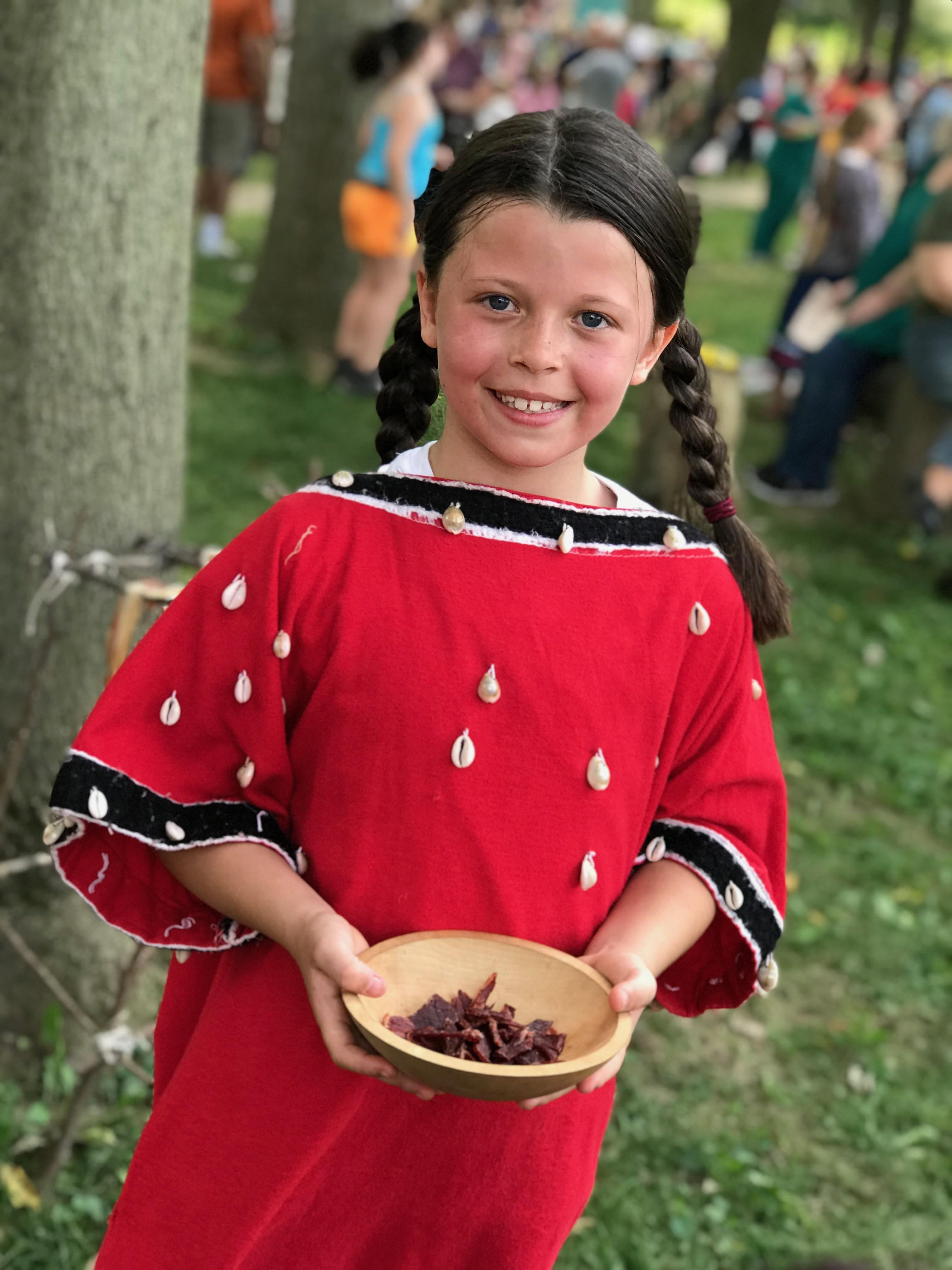 Smiling student dressed as a Native American and holding dried meat.