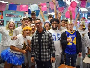 Mr. Beato standing with students