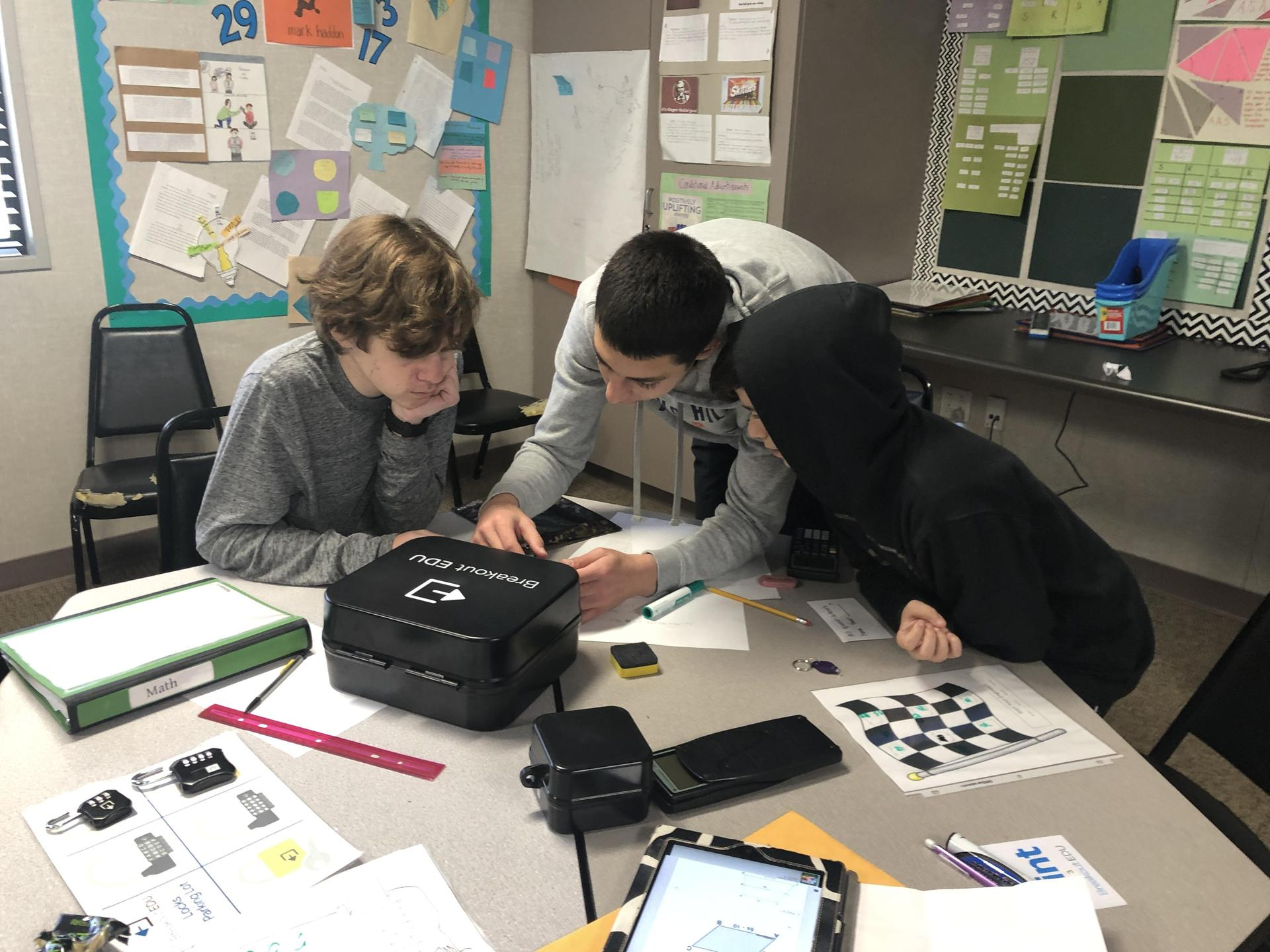 Math students working on a 'Breakout Box' activity that teaches through puzzle solving.