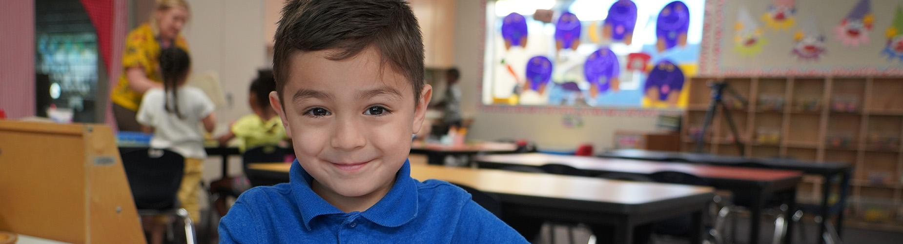 Child smiling in a classroom