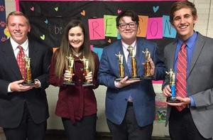 Four debate students with awards