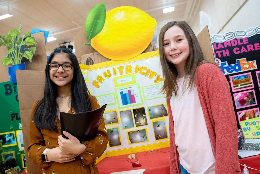 Two students stand in front of their project called Fruit-Tricity