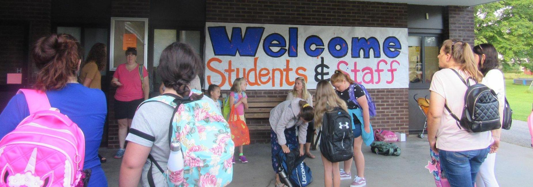 students walk into school; a sign that says WELCOME hangs in the background