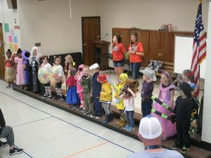 Kindergarten and first grade students lined up on stage for costume contest.