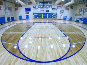 Inside a basketball gym showing the three point circle.  With the letters CHS showing on the stands behind the basketball hoop.