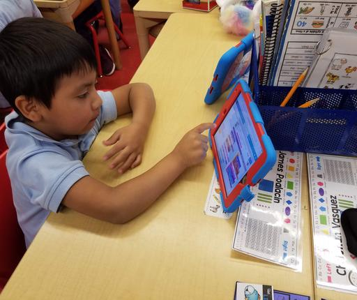One Kindergarten student Coding on tablet at his desk in classroom- CS4ALL Day 2019