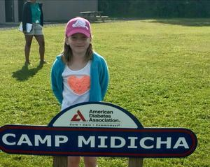 Rylee standing by the Camp Midicha sign