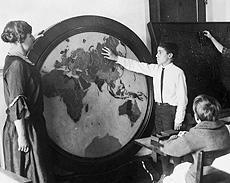 This picture from a 1918 reports shows a student using a large round wooden map of the world that is still being in a classroom 100 years later.