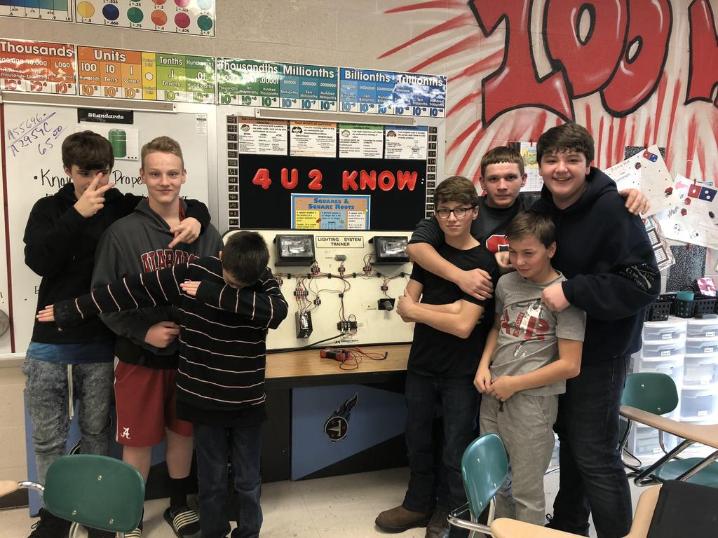 Middle school students pose with auto test board