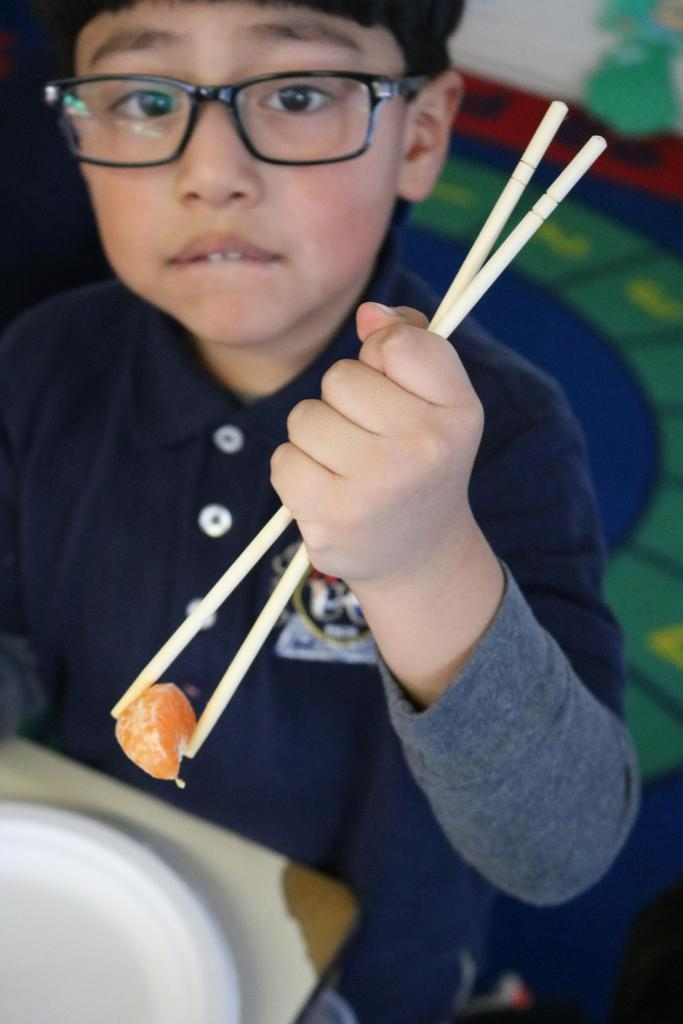 boy trying to pick up tangerine piece with chopsticks