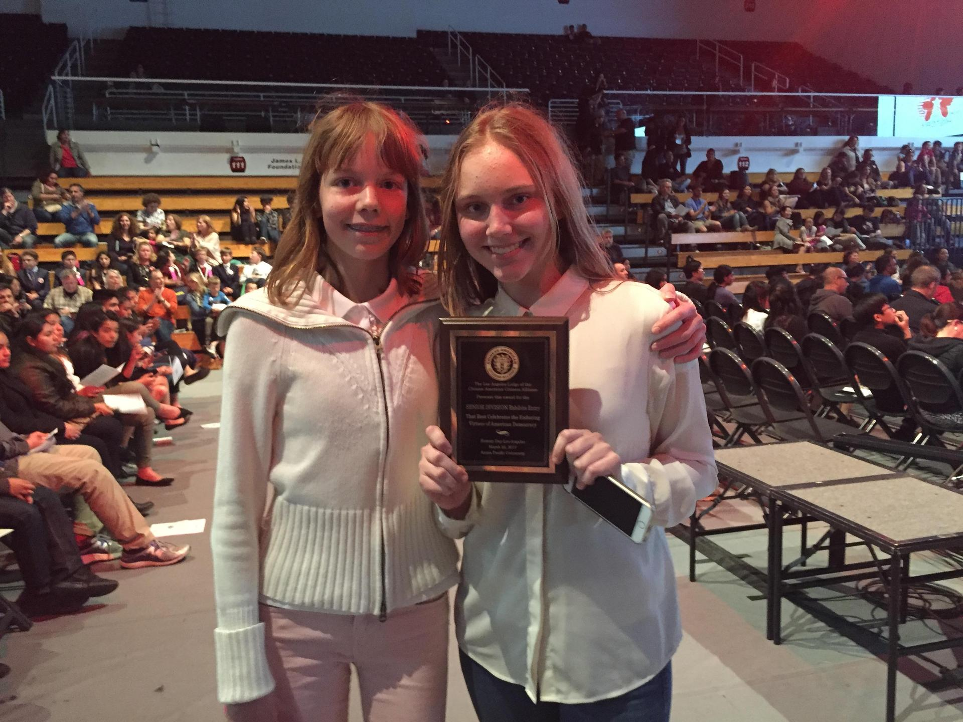 Two students holding up plaque award